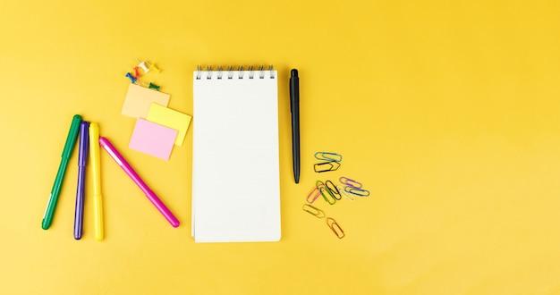 Bovenaanzicht van blanco notebook en schoolbenodigdheden zoals gekleurde markeringen, sticker en clipers op gele achtergrond, ruimte voor tekst.