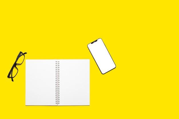 Bovenaanzicht van blanco notebook papier en smartphone scherm