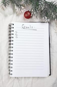 Bovenaanzicht van blanco notitieboekje voor doelenresoluties en kerstversiering op wit textiellinnen