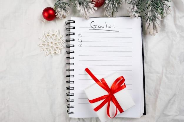 Bovenaanzicht van blanco notitieboekje voor takenlijst en kerstversiering op wit linnen tafelkleed