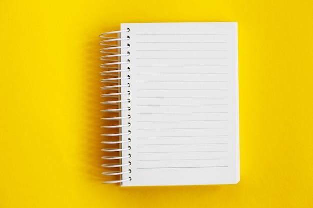 Bovenaanzicht van blanco notitiepapier op gele achtergrond