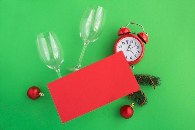 Bovenaanzicht van blanco rood papier voor kerstgroeten, wijnglazen en wekker