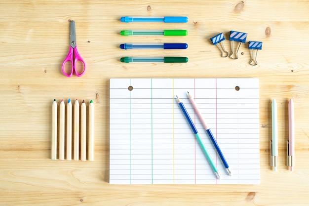 Bovenaanzicht van blanco vel papier, enkele clips, potloden, markeerstiften, pennen en schaar op houten tafel