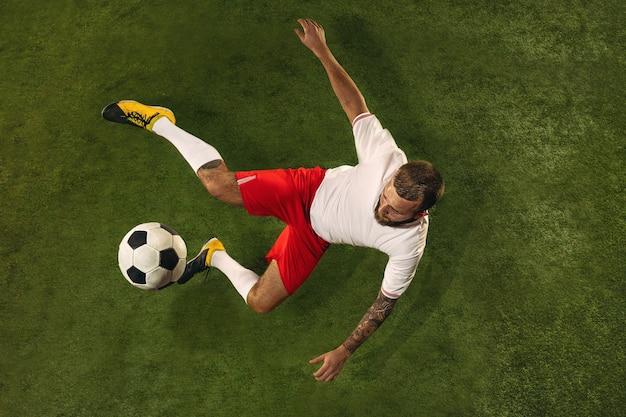 Bovenaanzicht van blanke voetbal of voetballer op groen