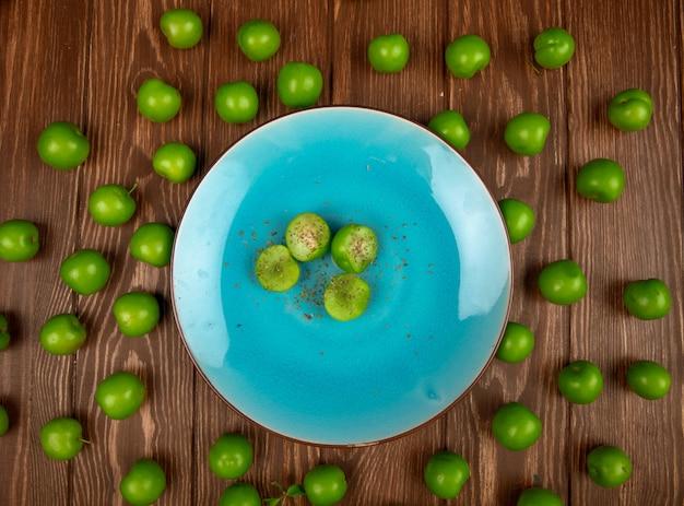 Bovenaanzicht van blauw bord met gesneden groene pruimen bestrooid met gedroogde pepermunt en zure groene pruimen gerangschikt rond op houten tafel