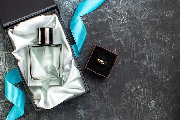 Bovenaanzicht van blauw lint op parfum voor mannen in een geschenkdoos en verlovingsband aan de rechterkant op donkere tafel