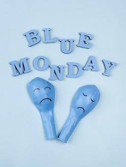 Bovenaanzicht van blauw maandag papier met trieste ballonnen