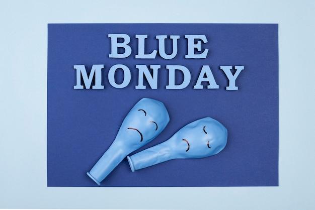 Bovenaanzicht van blauw maandagpapier met frowny ballonnen