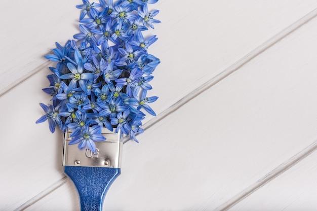 Bovenaanzicht van blauwe bloemensamenstelling en verfborstel