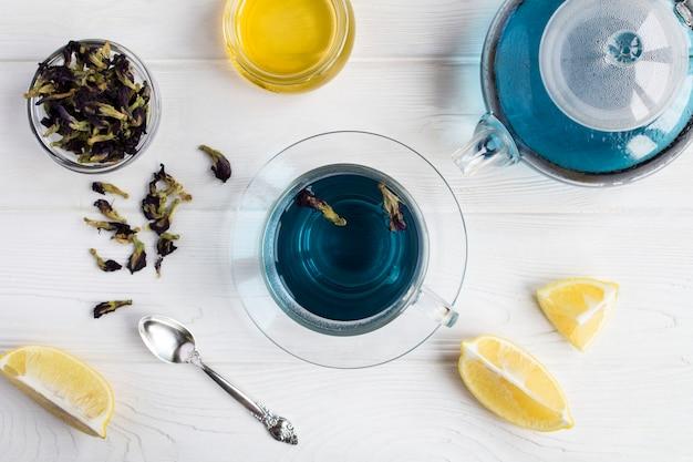 Bovenaanzicht van blauwe bloemthee in de glazen beker en theepot op het witte oppervlak