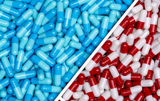 Bovenaanzicht van blauwe capsules en rood-witte capsules pillen in een plastic bakje. volledig frame van twee medicijnen. apotheek drogisterij producten. farmacologie concept. gezondheidszorg en medicijnen. farmaceutische industrie.