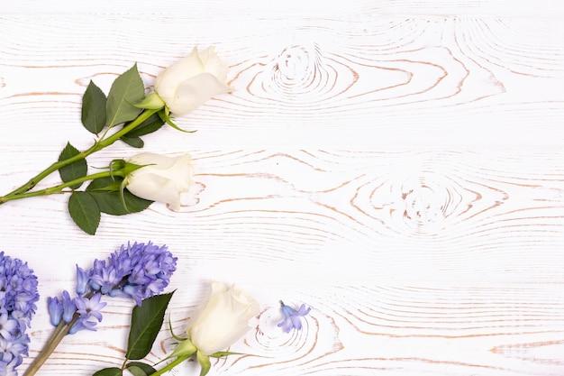 Bovenaanzicht van blauwe hyacint bloemen en witte rozen op een witte houten tafel