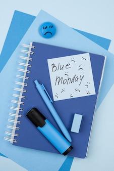Bovenaanzicht van blauwe maandag droevig gezicht met notitieboekje en marker