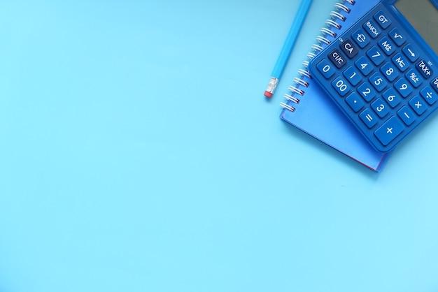 Bovenaanzicht van blauwe rekenmachine en kladblok op kleur achtergrond