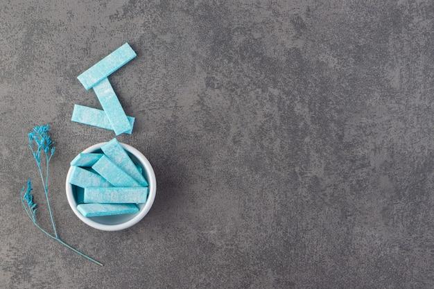 Bovenaanzicht van blauwe strip tandvlees op grijze ondergrond