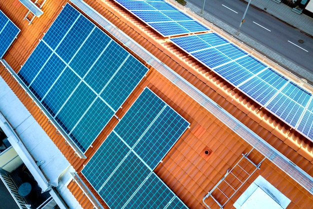 Bovenaanzicht van blauwe zonnepanelen op hoog flatgebouwdak.