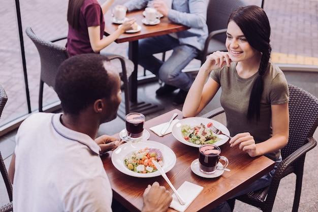 Bovenaanzicht van blij gelukkige paar salade eten zittend in café en vrouw haar gezicht aan te raken
