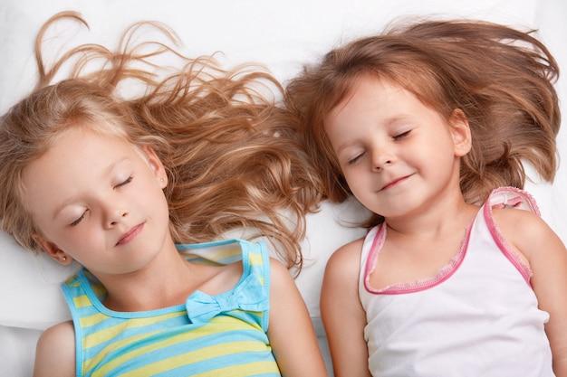 Bovenaanzicht van blije aantrekkelijke kleine meisjes of zussen lachen samen, slapen in bed, liggen dicht bij elkaar, zien aangename dromen, gekleed in nachtkleding. kinderen, relatie en vriendschap concept