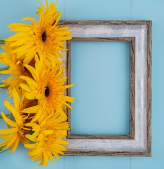 Bovenaanzicht van bloemen en frame op blauw met kopie ruimte