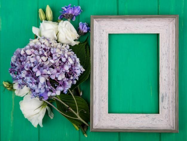 Bovenaanzicht van bloemen en frame op groene achtergrond met kopie ruimte