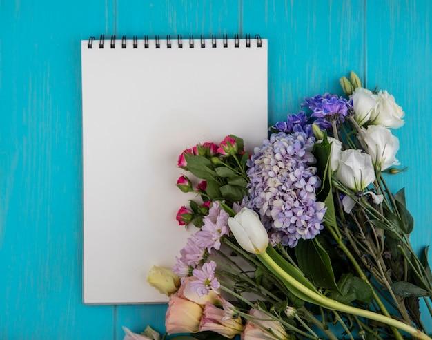 Bovenaanzicht van bloemen en notitieblok op blauwe achtergrond met kopie ruimte