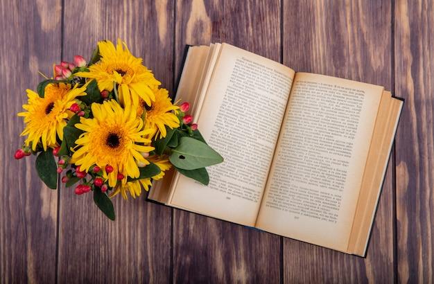 Bovenaanzicht van bloemen en open boek op hout