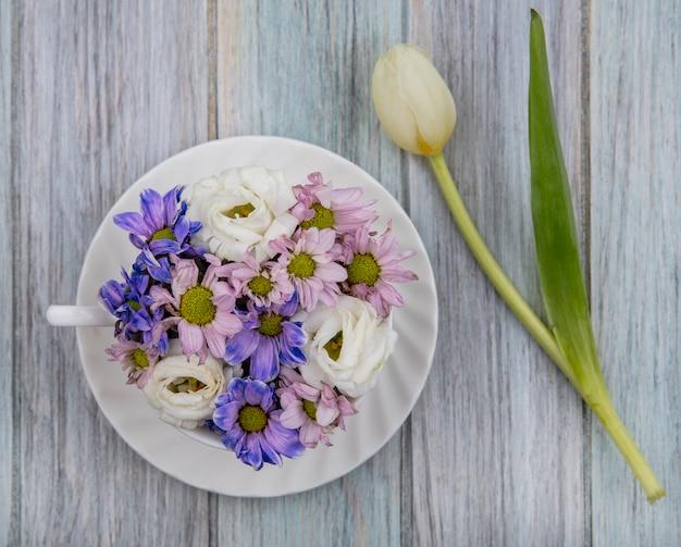Bovenaanzicht van bloemen in kop op schotel en op houten achtergrond