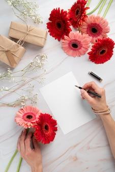 Bovenaanzicht van bloemen met blanco kaart en geschenken