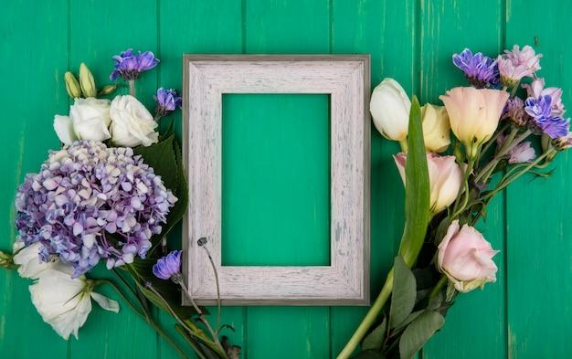 Bovenaanzicht van bloemen met frame in het midden op groene achtergrond met kopie ruimte