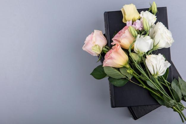 Bovenaanzicht van bloemen op gesloten boeken op grijze achtergrond met kopie ruimte