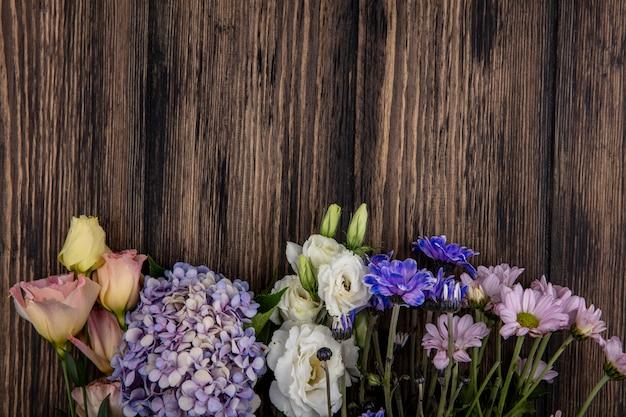 Bovenaanzicht van bloemen op houten achtergrond met kopie ruimte