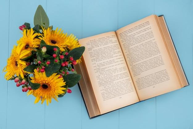 Bovenaanzicht van bloemen op open boek op blauw