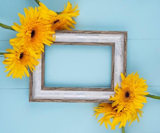 Bovenaanzicht van bloemen rond frame op blauw met kopie ruimte