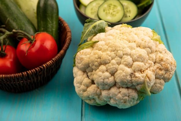 Bovenaanzicht van bloemkool met verse groenten zoals tomaten en komkommers op een emmer op een blauwe houten ondergrond