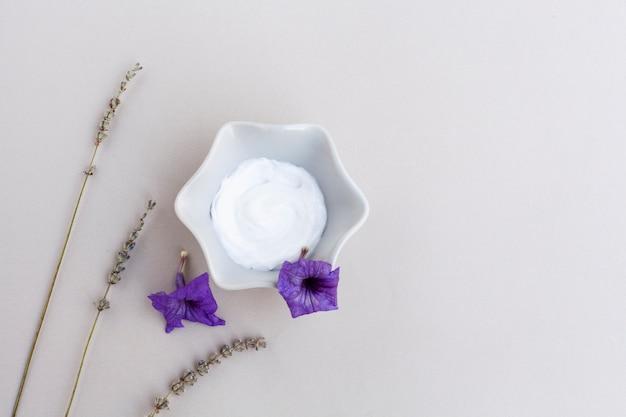 Bovenaanzicht van body cream en lavendel op effen achtergrond