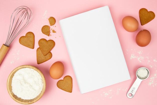 Bovenaanzicht van boek en koekjes op roze achtergrond