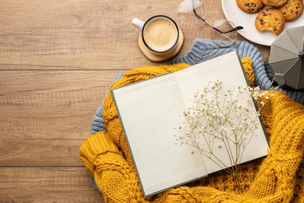 Bovenaanzicht van boek over truien met koekjes en kopje koffie