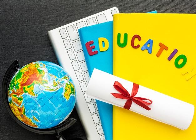 Bovenaanzicht van boeken met toetsenbord en diploma