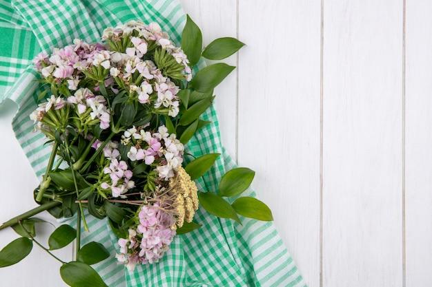 Bovenaanzicht van boeket bloemen op een groen geruite handdoek op een wit oppervlak
