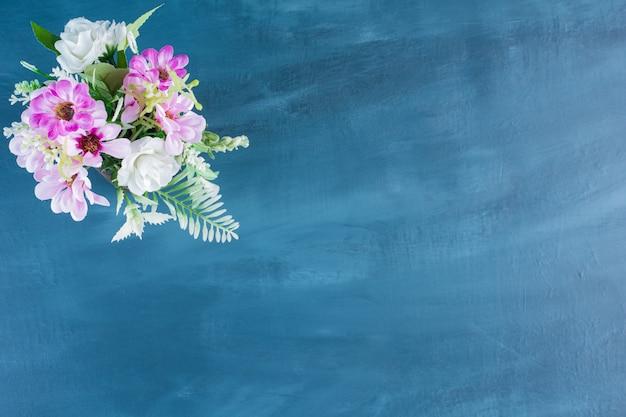 Bovenaanzicht van boeket van kleurrijke bloemen op blauwe achtergrond.