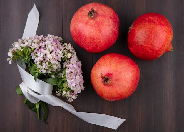 Bovenaanzicht van boeket van wilde bloemen met wit lint en granaatappels op een houten oppervlak