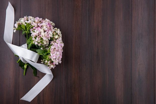 Bovenaanzicht van boeket van wilde bloemen met wit lint op een houten oppervlak
