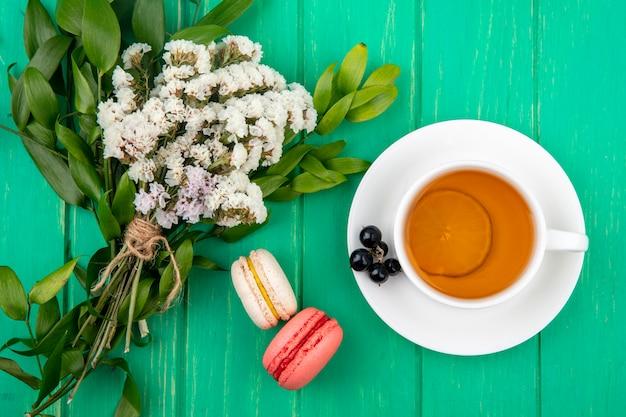 Bovenaanzicht van boeket van witte bloemen met een kopje thee met macarons op een groen oppervlak