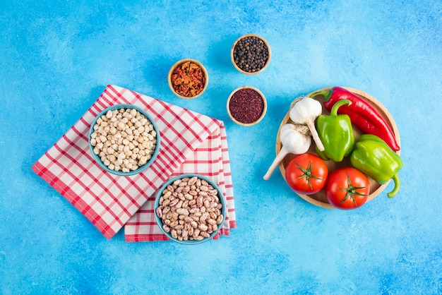 Bovenaanzicht van bonen en kikkererwten in kom en verse groente met kruiden op blauwe achtergrond.