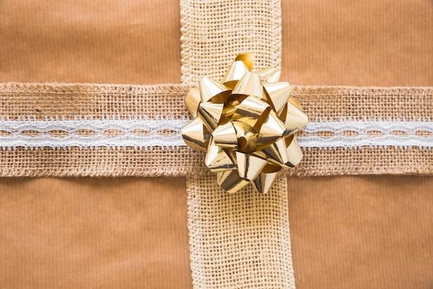 Bovenaanzicht van boog en weven lint op bruin geschenk papier