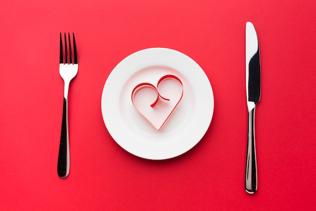 Bovenaanzicht van bord met papieren hartvorm en bestek