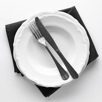 Bovenaanzicht van borden met bestek en servet