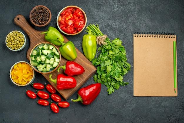 Bovenaanzicht van bordstandaard met groenten erboven en dichtbij en blocnote aan de zijkant op een donkere grijsachtige achtergrond