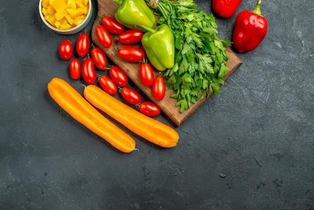 Bovenaanzicht van bordstandaard met groenten erboven en ernaast met vrije plaats voor uw tekst op donkergrijze achtergrond