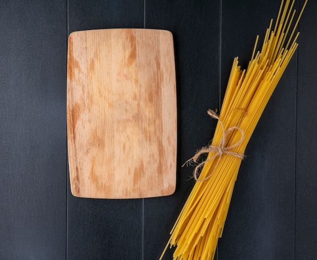 Bovenaanzicht van bos van rauwe spaghetti met schoolbord op zwarte ondergrond